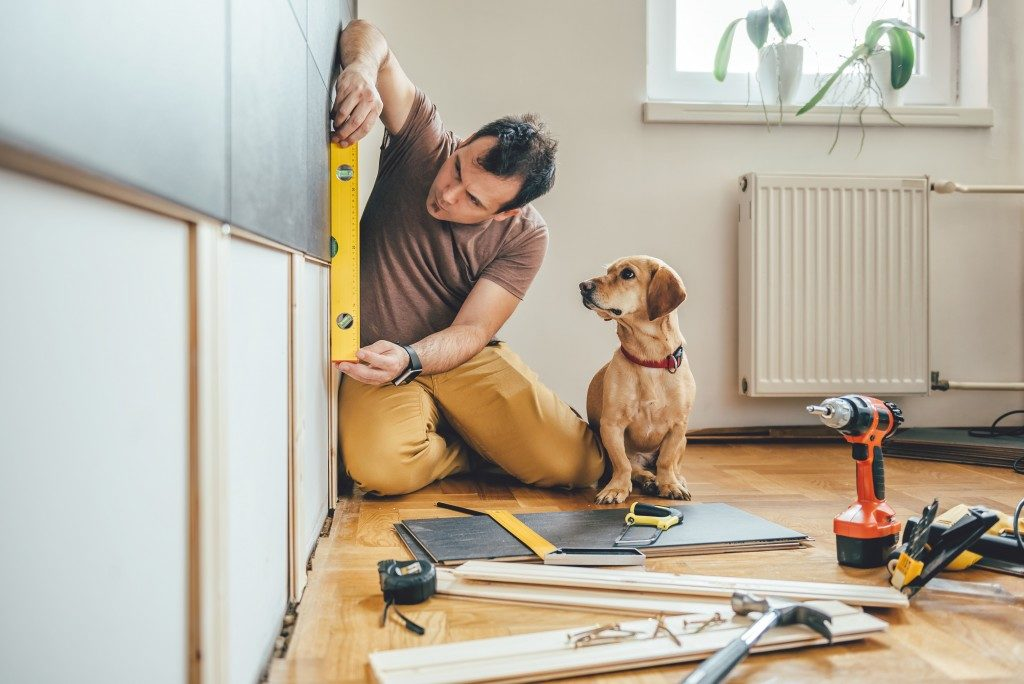 man doing DIY work with dog